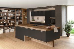 Une cuisine avec ilot ouverte sur l'intérieur de la maison ainsi qu'une grande bibliothèque